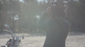 Back view of the young woman putting on the motorcycle helmet standing at her new motorbike in soft light. Hobby. Traveling and active lifestyle. Female biker stock footage