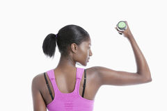 Back view of young woman raising dumbbell over white background Royalty Free Stock Image