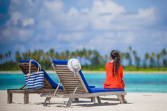 Back view of young woman relaxing at beach chairs. Back view of young beautiful woman relaxing at beach chairs Royalty Free Stock Photo