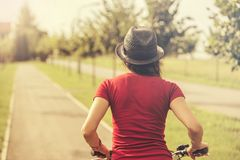 Back view of young woman riding on bike Stock Images
