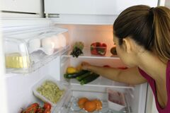 Back view of young woman searching for heathy food in the fridge