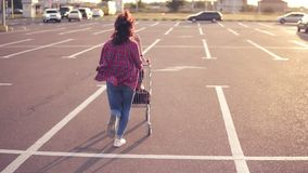 Back view of a young woman sitting in the grocery cart, while her friend is pushing her behind in the parking by the. Shopping mall, enjoying outdoors with stock footage