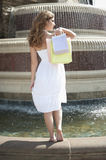 Back view of a young woman standing by fountain carrying shopping bags Royalty Free Stock Image