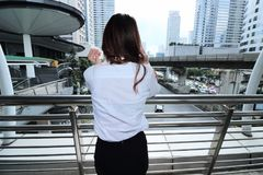 Back view of young woman standing and looking far away in urban city background. Stock Photos