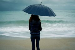 Back view of Young woman standing with an umbrella in front sea. In winter or autumn stock photo