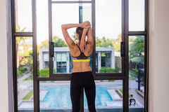 Back view of young woman stretching doing morning workout at luxury hotel resort with a great view. Female model doing Stock Images