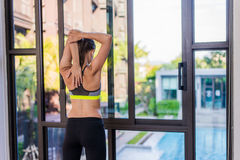 Back view of young woman stretching doing morning workout at luxury hotel resort with a great view. Female model doing Royalty Free Stock Image