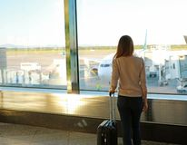 Back view young woman with suitcase in modern airport terminal royalty free stock photography