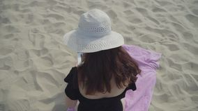 Back view of young woman in the summer white hat working with laptop on the beach. Freelance concept. Busy woman on stock video