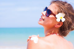 Back view of Young woman in sunglasses putting sun Royalty Free Stock Image