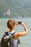 Back view of young woman taking photos with mobile phone. Stock Photo
