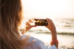 Back view of a young woman taking a picture. Of a sunset at the beach with mobile phone Stock Photography