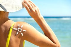 Back view of young woman tanning at the beach with sunscreen cream in sun shape on her shoulder. UV sunburn protection and
