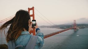 Back view young woman tourist with backpack, wind in hair takes smartphone photo of Golden Gate Bridge San Francisco. Excited happy female traveler enjoying stock video
