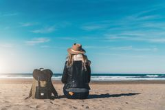 Back view. Young woman tourist in hat and with backpack sitting on beach and looking at sea, on coastline, on horizon. Tourism, vacation, lifestyle, relaxing Royalty Free Stock Photography