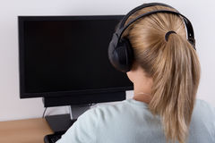 Back view of young woman using a computer and listening music Royalty Free Stock Photography