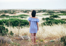Back view of young woman walking on beautiful valley and sea lan Stock Photo