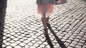 Back view of young woman walking in city centre in streets with paving stones. Stylish girl spending time alone. Back view of young woman walking in city centre stock video