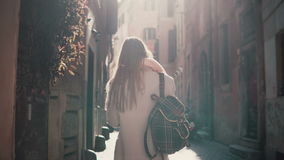 Back view of young woman walking at city street in Europe at morning. Girl exploring the old town alone, looking around.