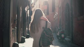 Back view of young woman walking at city street in Europe at morning. Girl exploring the old town alone, looking around. Back view of young man walking at city Royalty Free Stock Photo