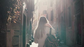 Back view of young woman walking at city street in Europe at morning. Girl exploring the old town alone, looking around. Stock Photos