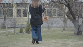 Back view of young woman walking with the wicker basket of walnuts holding brush in hand. Attractive artist in flared. Pants and long shirt walks on heels stock video