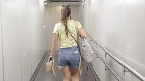 Back view of young woman walking the aisle on plane. Back view of young woman wearing formal suit walking the aisle on plane stock video footage