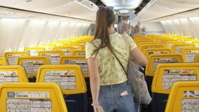Back view of young woman walking the aisle on plane. Back view of young woman wearing formal suit walking the aisle on plane stock video