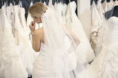 Back view of a young woman in wedding dress looking at bridal gowns on display in boutique Stock Photo