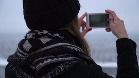 Back view of young woman in winter hat and warm coat making photo of beautiful landscape. Background blurred. Girl. Back view of young woman in winter hat and stock footage