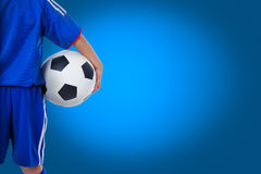 Back view of youth soccer player in blue uniform. And little kid holding a ball. Some space for input text message on blue background Royalty Free Stock Image