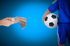 Back view of youth soccer player and hand holding stacks of bank. Back view of youth soccer player in blue uniform and little kid holding a ball and hand holding Stock Photo