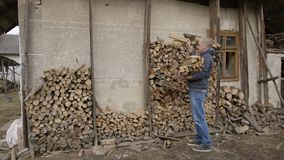 Back in the village in Ukraine man comes into the wood to ignite in the oven. stock footage