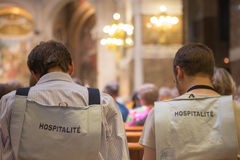 Back of volunteers in Lourdes in the church of Lourdes. Back of volunteers in Lourdes in the church. Volunteer helpers in Lourdes are welcoming and friendly. The Stock Image
