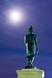 Back of walking Buddha statue in twilight Stock Photo