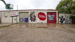 Back wall of a building with multiple graffiti style murals in West Dallas, Texas.