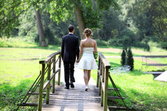 Back of wedding couple walking. Wedding couple is walking on a bridge after her marriage whith shirt mini dress skirt. short wedding gown Royalty Free Stock Image
