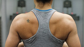 Back of a weightlifter as she pulls weights from a machine Stock Photo