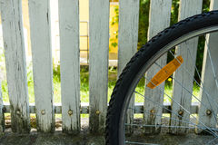 Back wheel of bicycle in front of white fence Royalty Free Stock Images