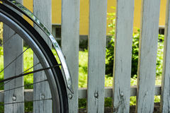 Back wheel of bicycle in front of white fence Stock Photos