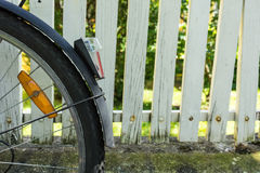 Back wheel of bicycle in front of white fence Stock Photography