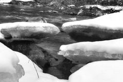 Back and white photo of river with frozen ice blocks and snow on its banks Royalty Free Stock Photos