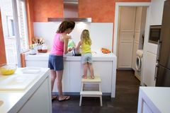 Back of woman and child cooking together in the kitchen Royalty Free Stock Photos