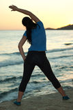 Back of woman doing fitness at sunset. On th beach royalty free stock image
