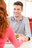 Back of woman holding biyfriend's hand at restaurant. Royalty Free Stock Photo