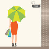 Back of woman holding shopping bags and umbrella with sale sign. Royalty Free Stock Images