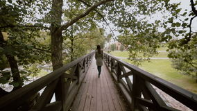 A back of a woman with long dark hair who is walking on a long wooden bridge. stock video footage