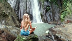 Back of woman meditating at the beautiful waterfall in green tropical rain forest in Bali stock video