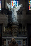 Back woman praying in church. In front of the sculpture of the Angel Royalty Free Stock Photos