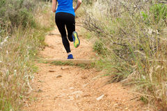 Back of woman running on dirt path Royalty Free Stock Photo